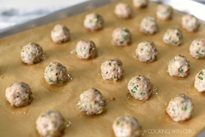 Baked pork meatballs on a parchment lined baking sheet