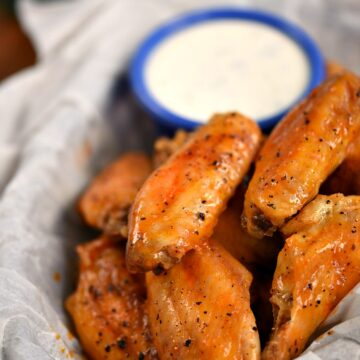 Baked Buffalo Chicken Wings with a side of Ranch dressing in a parchment paper lined basket
