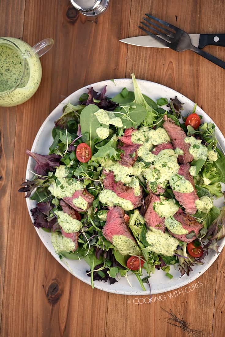 Looking down on a Cilantro-Lime Steak Salad, a carafe of cilantro-lime dressing.