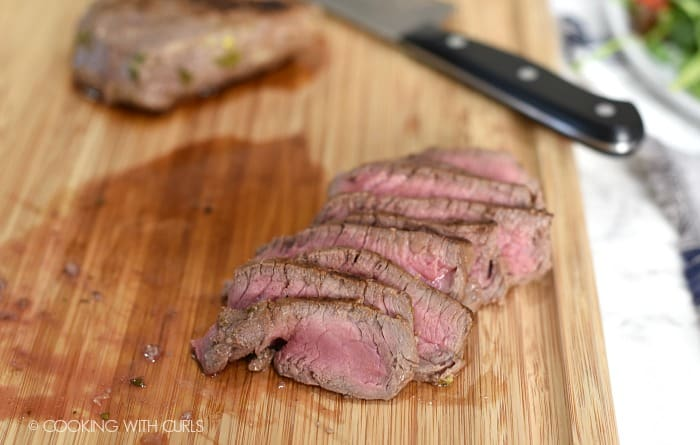 Thinly sliced steak on a wooden cutting board.