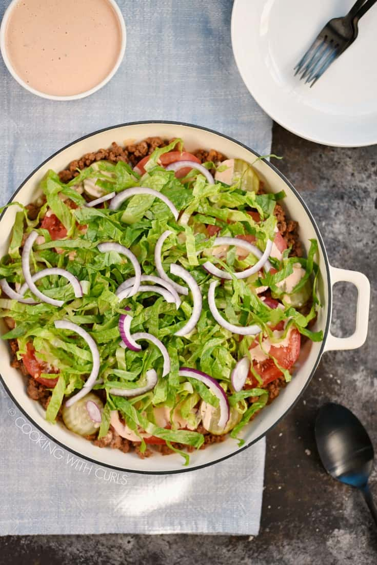 Looking down on shredded lettuce, sliced red onion, tomatoes, pickles and ground beef in a large white skillet
