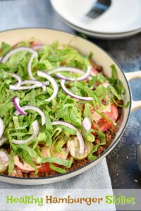 A large white skillet filled with shredded lettuce, thinly sliced onions, pickles and tomato slices on top of a hamburger mixture and cauliflower rice
