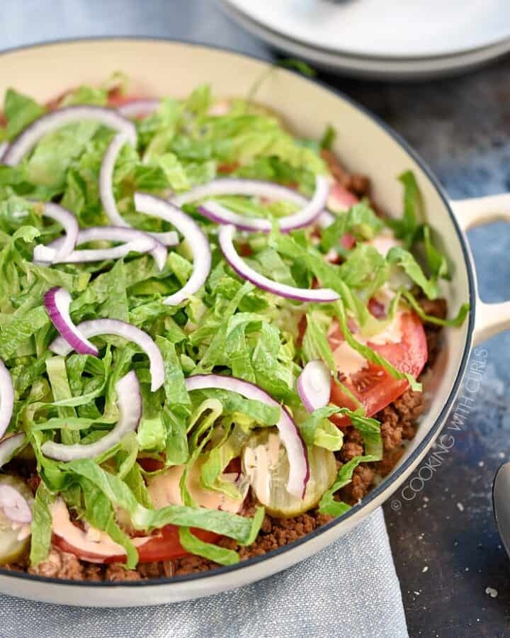 A skillet filled with ground beef, tomato and pickle slices, shredded lettuce and thinly sliced onions