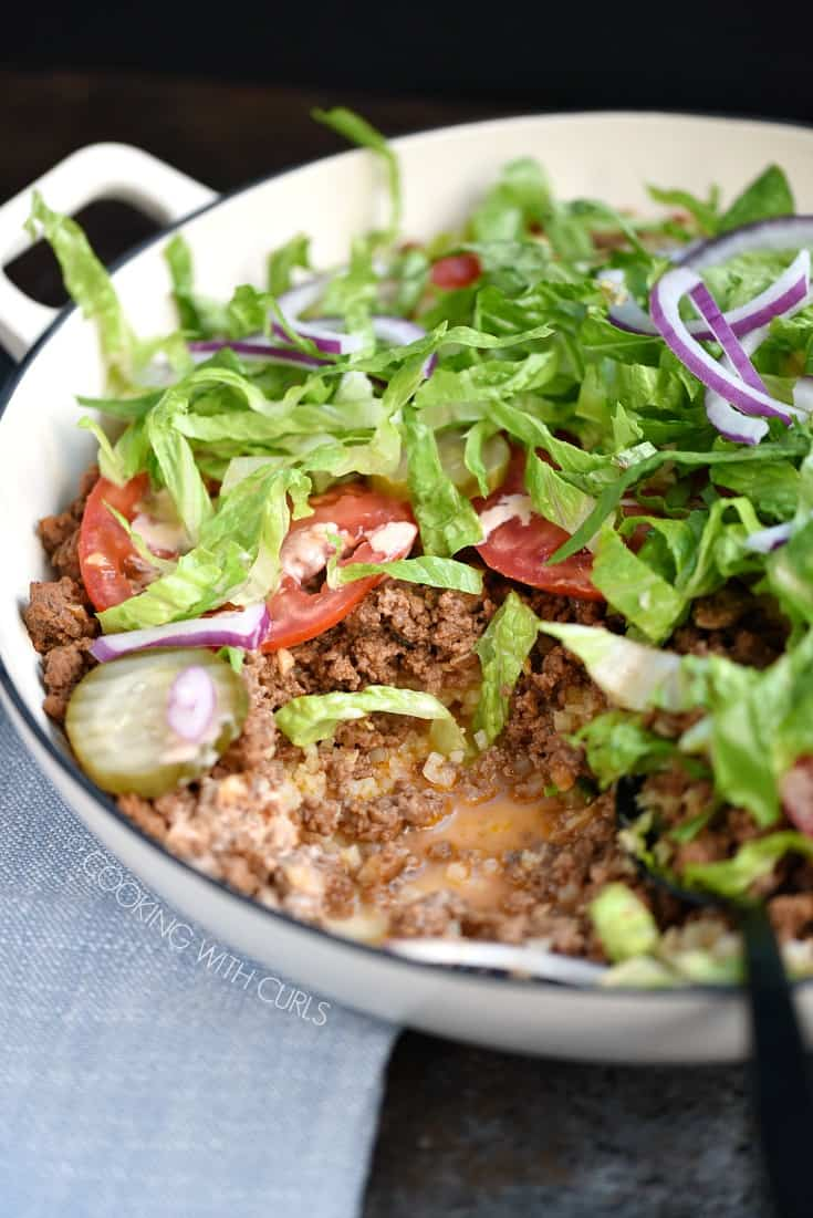 Layered cauliflower rice, hamburger, tomato, pickles, shredded lettuce and onion slices in a large white skillet.