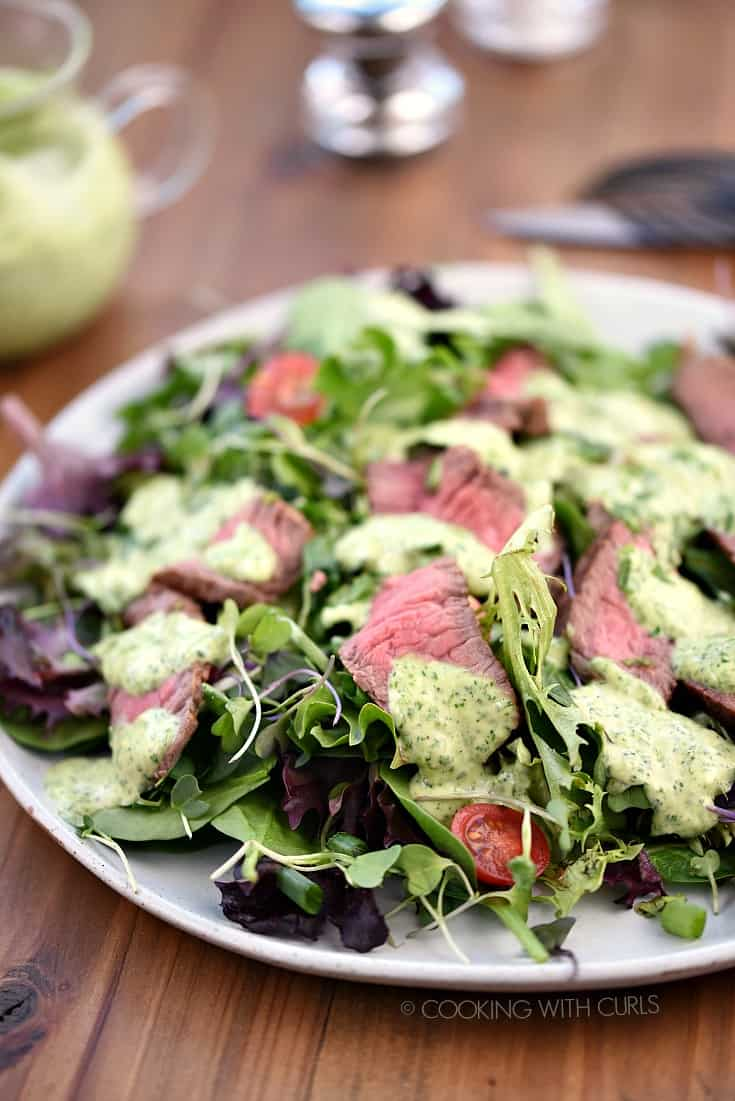 A large white plate topped with salad greens, sliced steak, cherry tomatoes and cilantro-lime dressing
