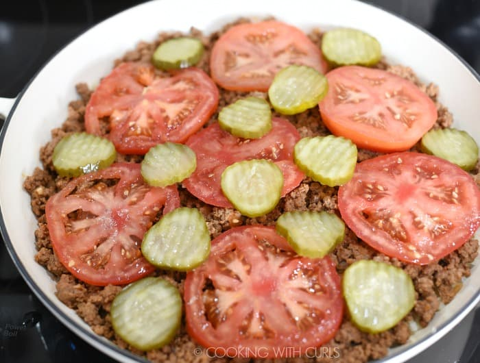 Tomato and pickle slices on top of the cooked hamburger meat in a large skillet.