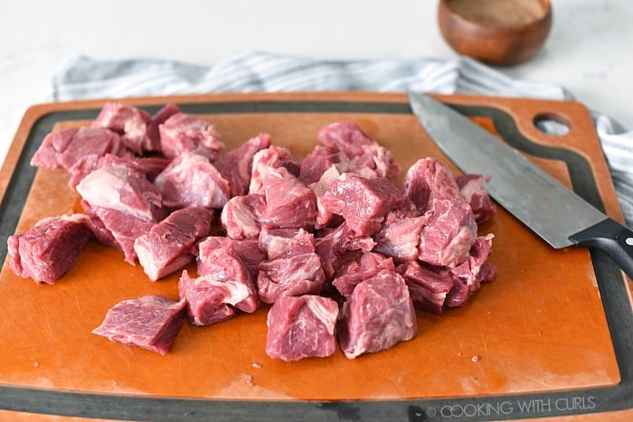 Beef chuck cut into cubes with a sharp knife on a cutting board.