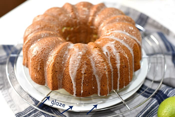 Glaze drizzled over the bundt cake on a wire cooling rack, on top of a large white plate.