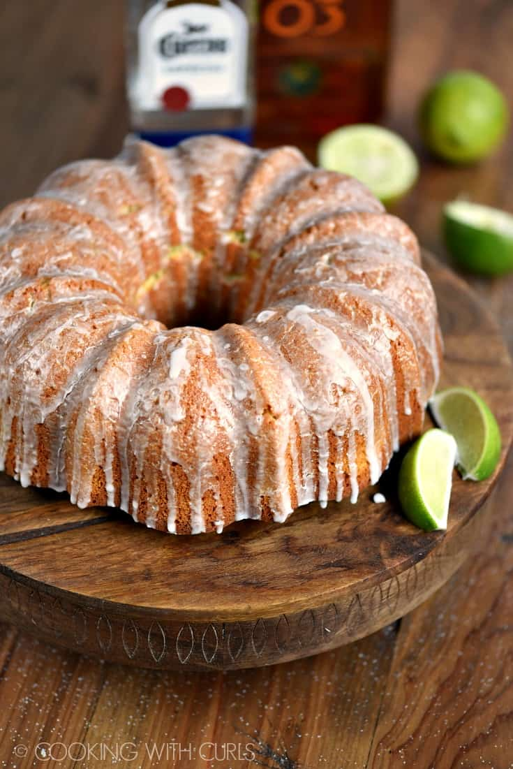 Margarita Bundt Cake displayed on a wooden cake platter with lime on the side and in the background.