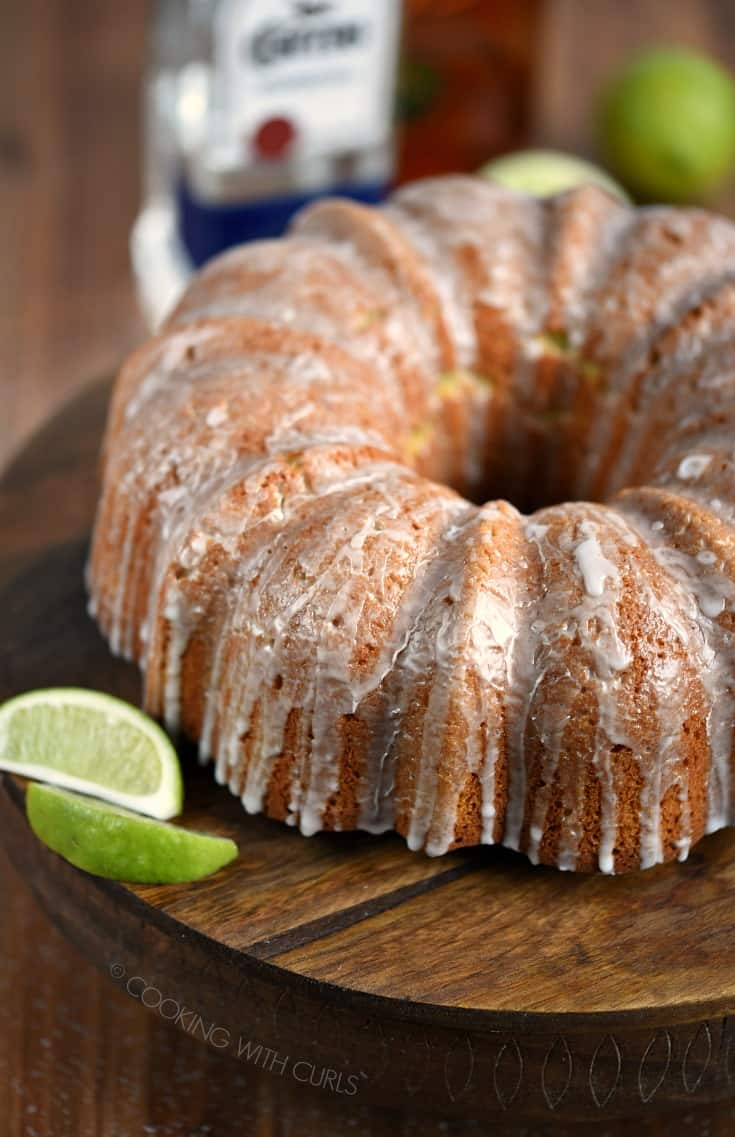 A Margarita Bundt Cake displayed on a wooden cake plate with lime slices on the side.