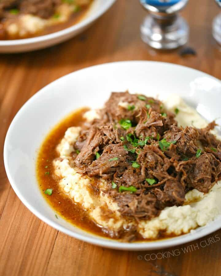 Two bowls of Instant Pot Cafe Mocha Pot Roast served over mashed cauliflower