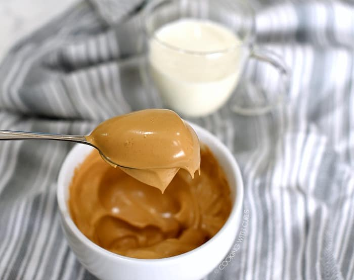 A scoop of the whipped coffee mixture on a large spoon hovering over a white bowl.