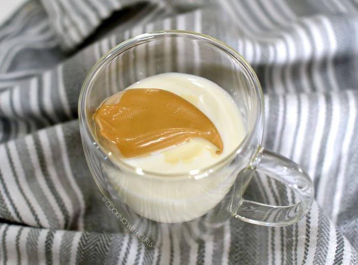 A scoop of whipped coffee mixture floating on top of milk in a clear glass mug.