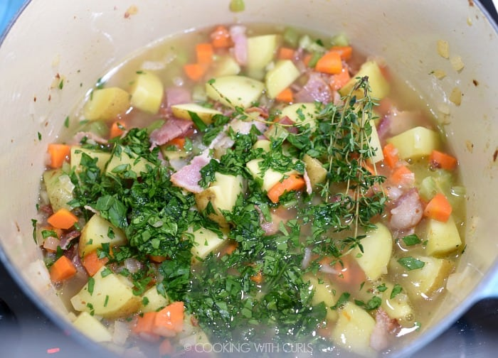Chicken stock, parsley and thyme added to the vegetables in a large pan.