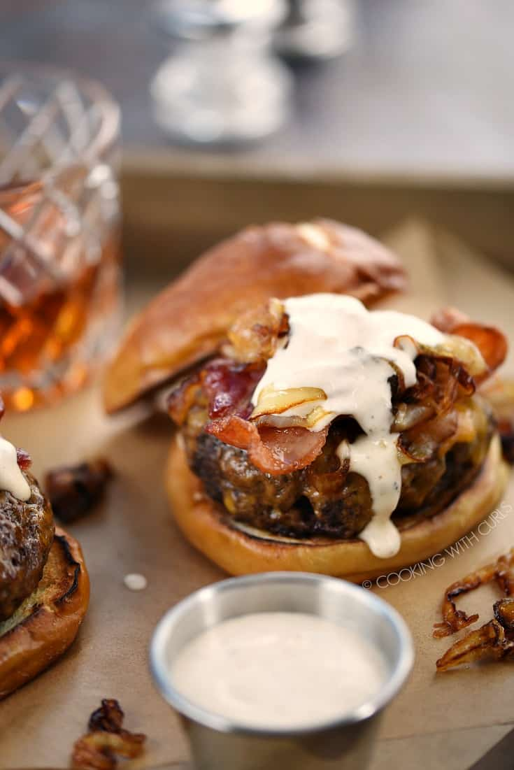 Crispy bacon, cheddar cheese, grilled onions and whiskey aioli top these half pound beef patties on pretzel buns.