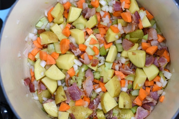 Diced onions, celery, carrots and potatoes added to the cooked bacon in a large pan.