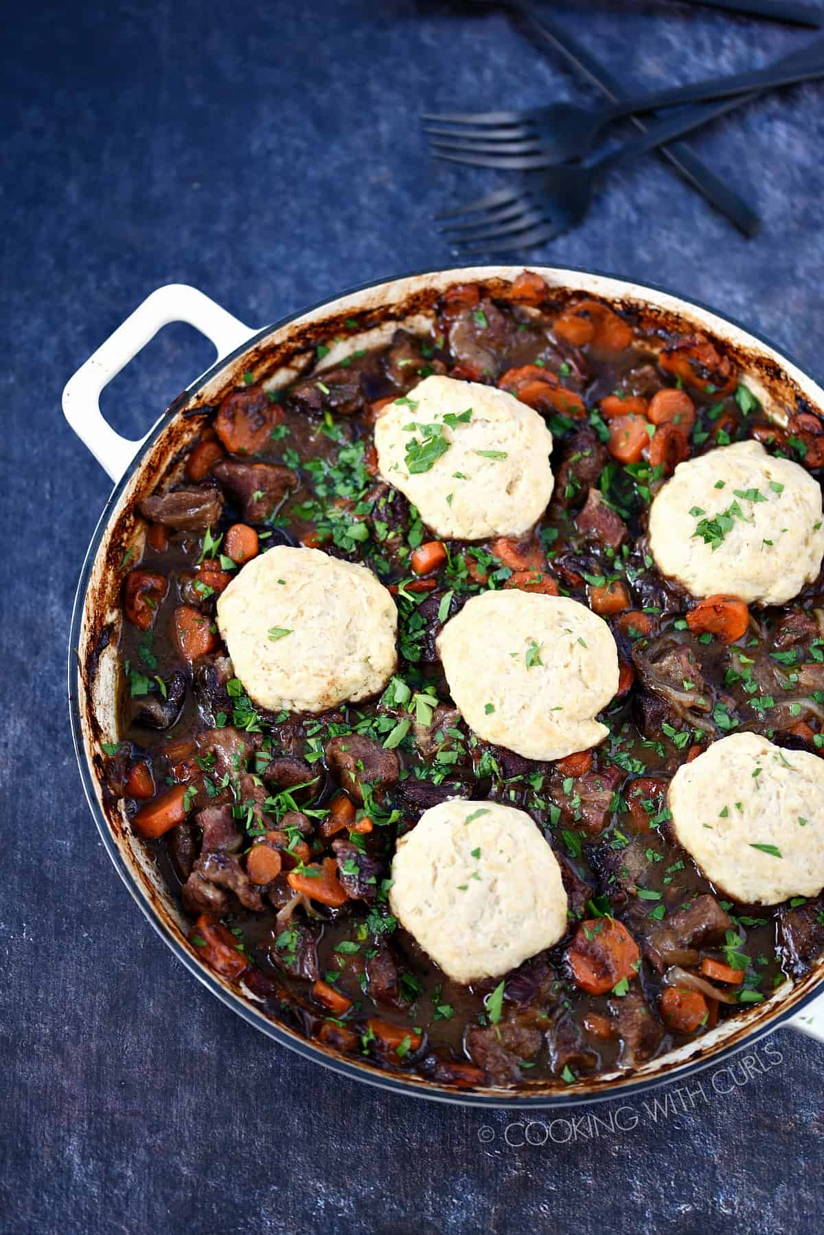 Looking down on a casserole pan filled with Guinness Beef, carrots and onions topped with Herb Dumplings.