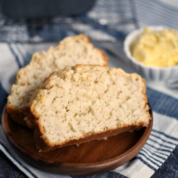 Closeup image of two slices of Homemade Beer Bread on a wood plate with a bowl of butter in the background.