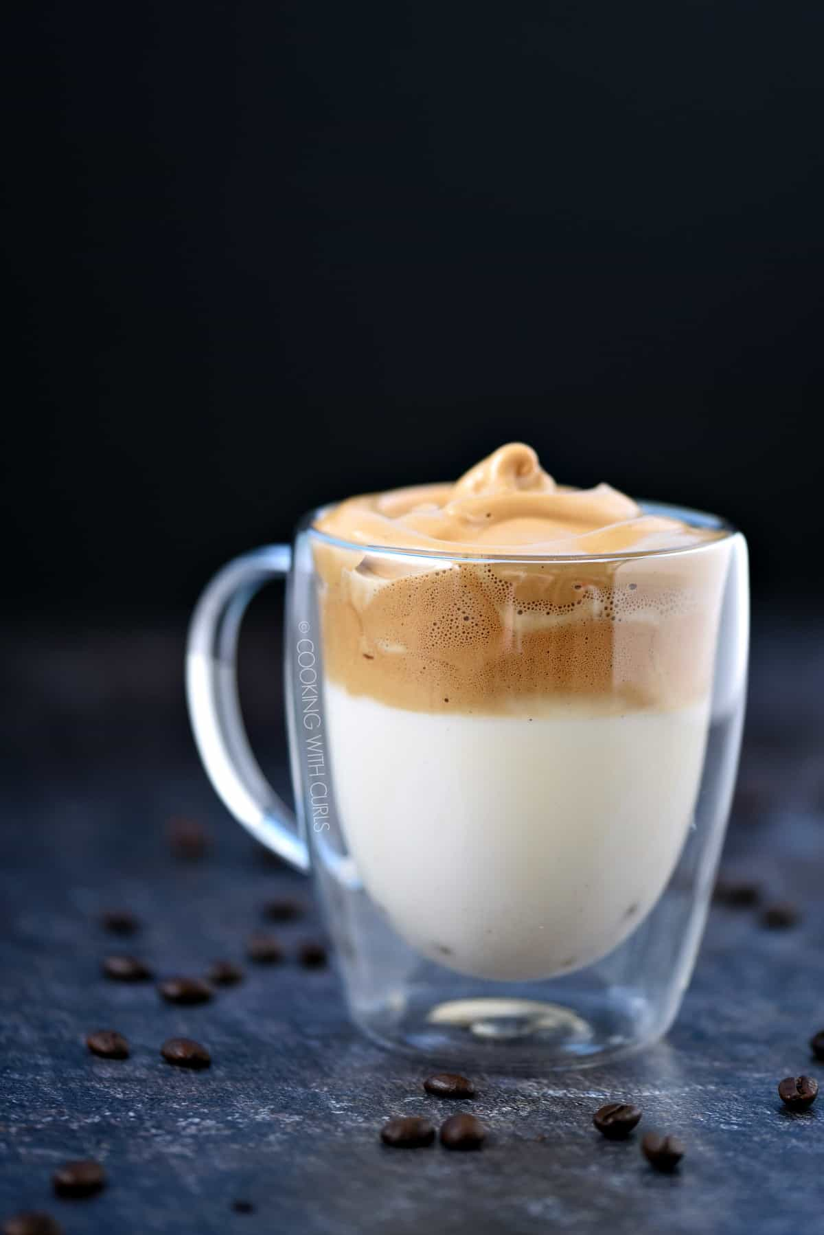 A layer of milk topped with a layer of Whipped Dalgona Coffee in a clear glass mug.