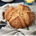 Irish Brown Soda Bread on a beige napkin with white plates and softened butter in the background.