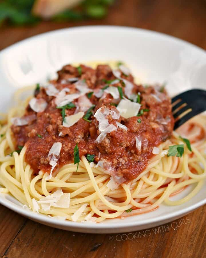 Spaghetti noodles topped with Simple Bolognese Sauce and grated Parmesan cheese.