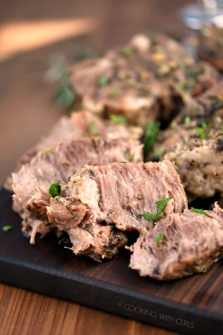 A close up image of sliced Instant Pot Rosemary Garlic Pork Roast on a wood cutting board.