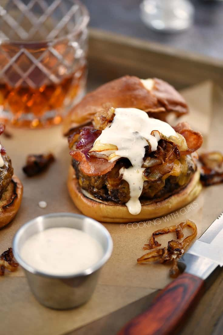 A burger topped with grilled onions, bacon, and whiskey mayonnaise on a pretzel bun with a glass of whiskey in the background.