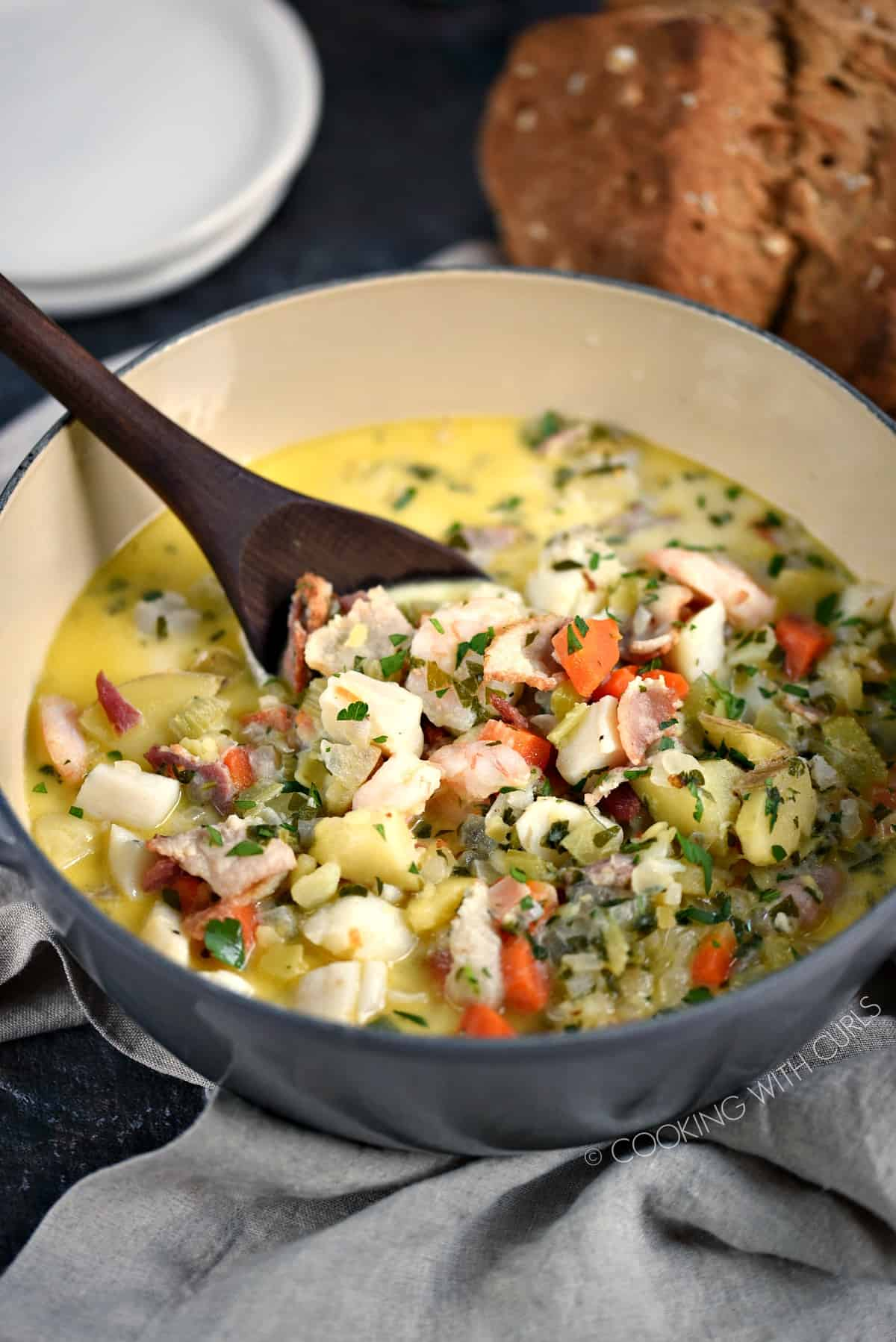 Creamy Seafood Chowder with a loaf of brown soda bread in the background.