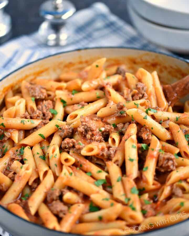 Sloppy Joe Pasta Skillet on a blue and white napkin with empty white bowls in the background.