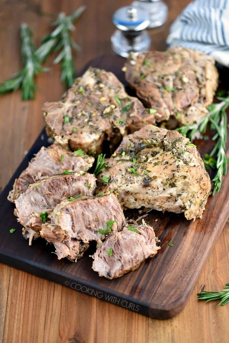 Instant Pot Rosemary Garlic Pork Roast served on a wooden cutting board.