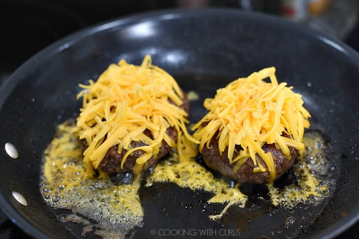 Two half-pound burgers topped with shredded, cheddar cheese in a skillet.