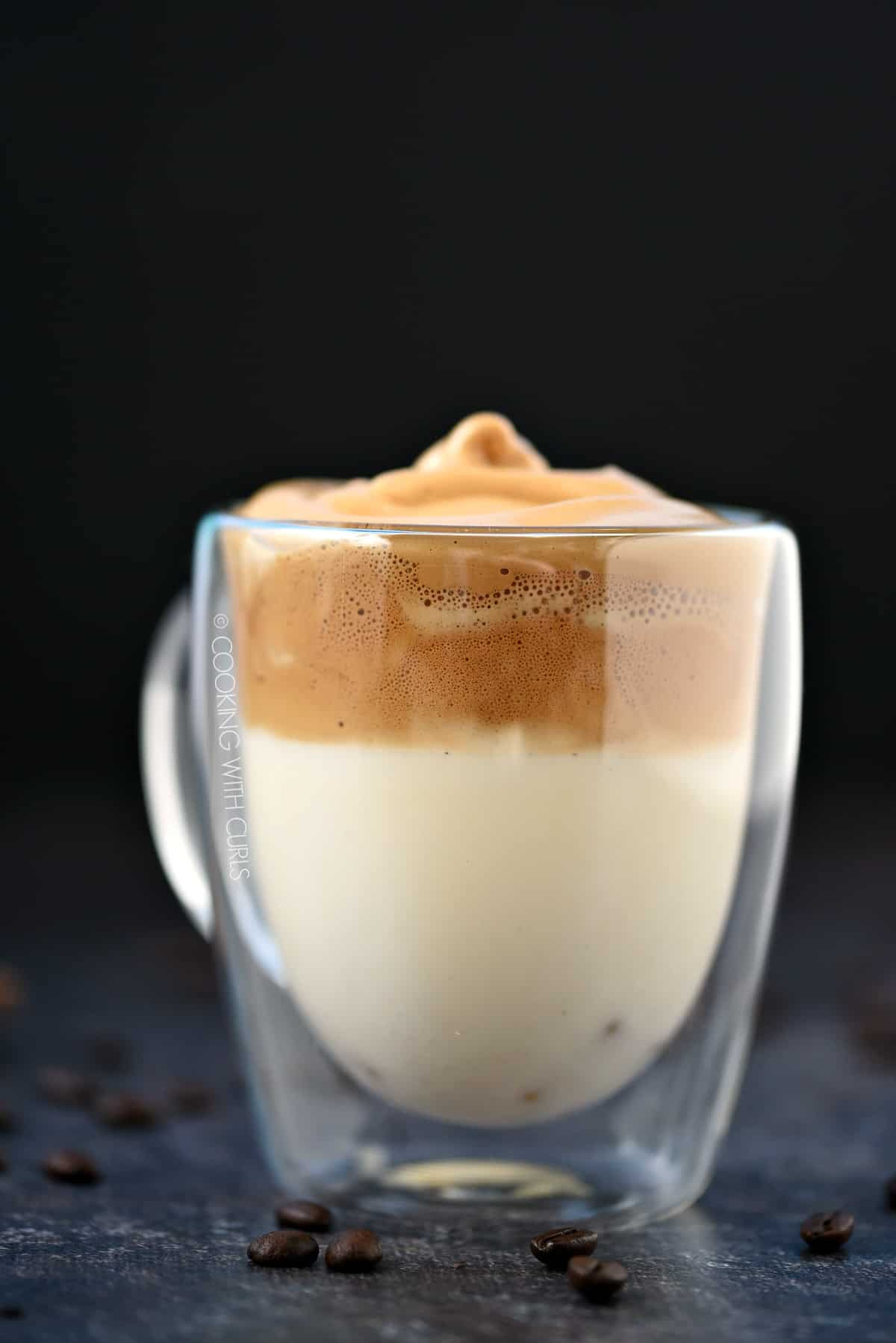 Side view of whipped dalgona coffee floating on top of milk in a clear glass mug.