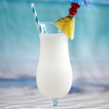 Creamy Pina Colada Milkshake in a hurricane glass garnished with a pineapple wedge, two cherries and a blue umbrella.