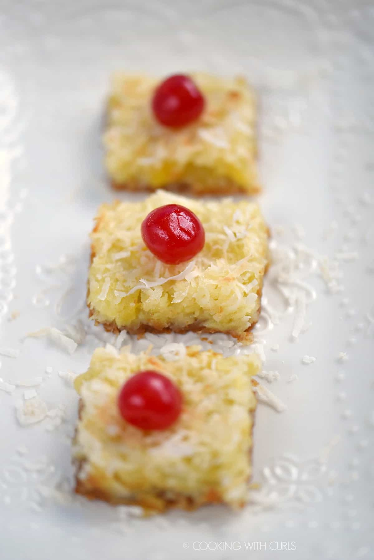Three cherry topped Pina Colada Bars lined up on a white plate.