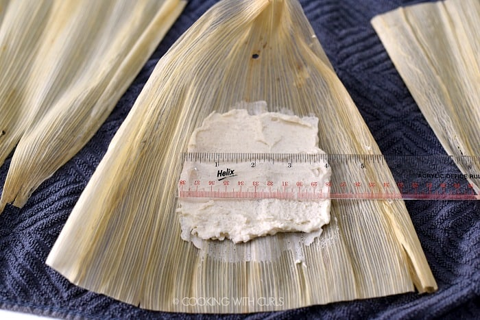 Masa mixture spread onto a corn husk in a 4 inch square.