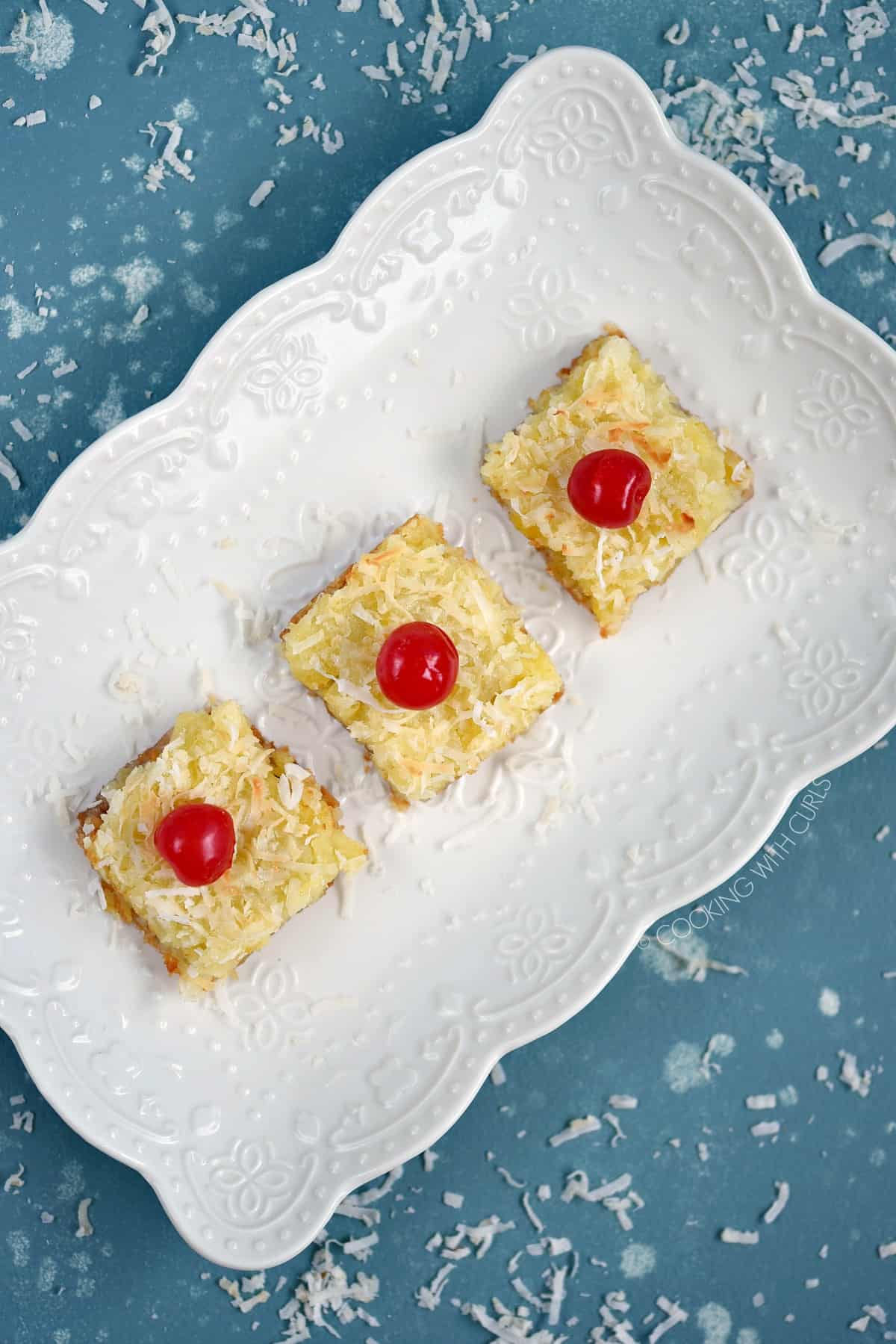 Looking down on three cherry topped Pina Colada Bars lined up on a white serving platter.