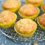 Pina Colada Muffins in yellow wrappers sitting on a wire cooling rack.