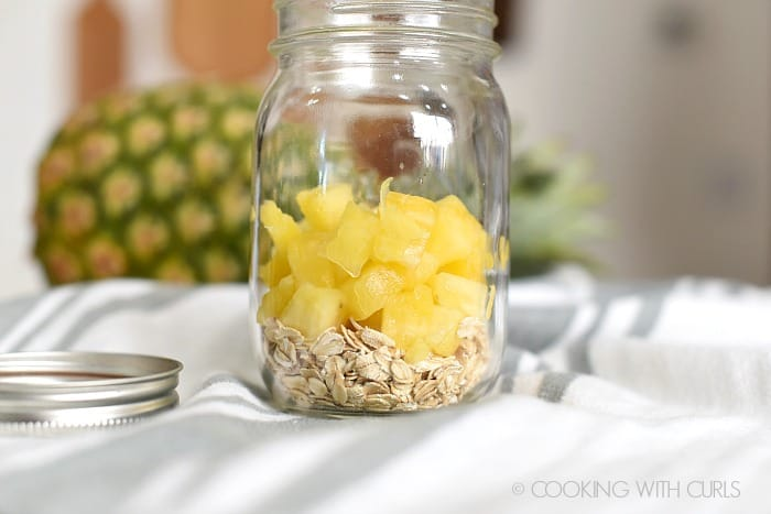 Rolled oats and fresh pineapple chunks in a glass mason jar.