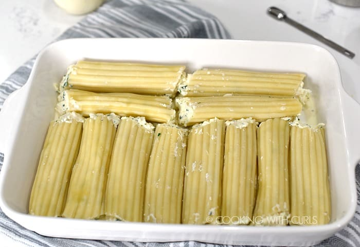 Twelve manicotti tubes stuffed with chicken filling and lined up in a white baking dish.
