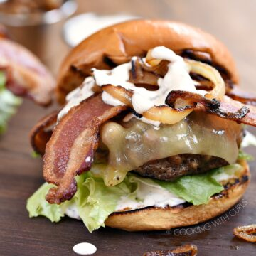 Grilled Double Bacon Burgers with lettuce, tomato, caramelized onions, white cheddar, strips of bacon and white barbecue sauce sitting on a wooden board.
