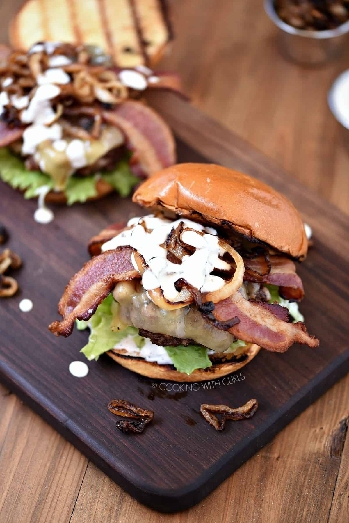 Looking down on two Grilled Double Bacon Burgers topped with caramelized onions and white barbecue sauce sitting on a wood board.