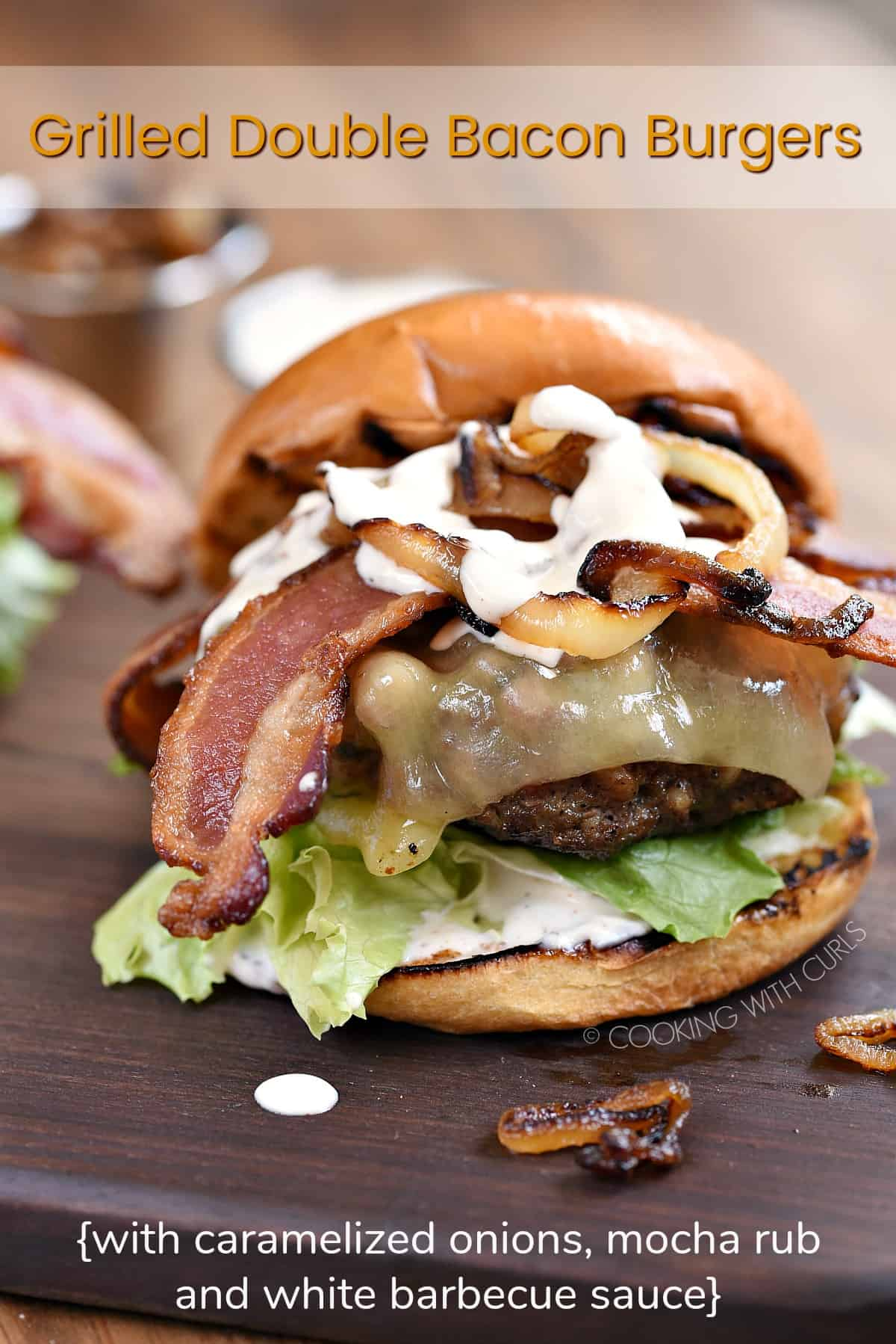 Grilled Double Bacon Burgers on grilled buns, topped with lettuce, tomato, caramelized onions and white barbecue sauce sitting on a wood board with a title graphic across the top.