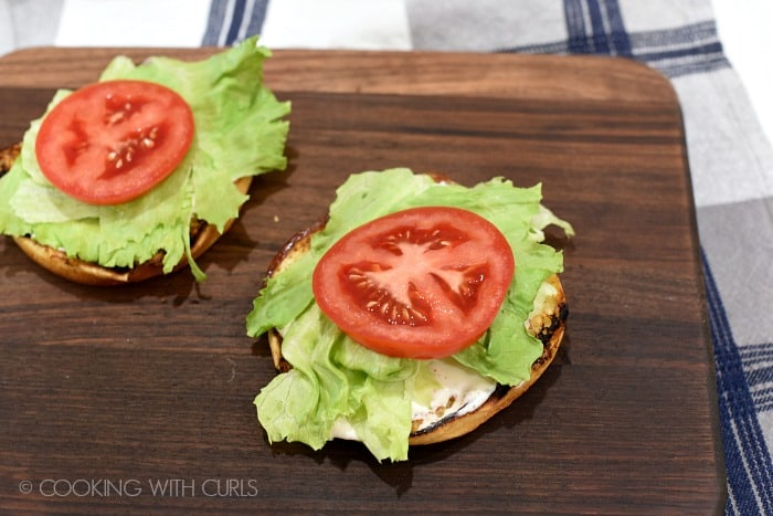 Lettuce and a tomato slice on top of the grilled burger buns sitting on a walnut cutting board.