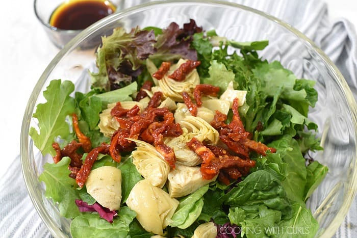 Mixed greens, artichoke hearts and sliced sun-dried tomatoes in a large glass bowl with dressing in a small bowl in the left hand corner.