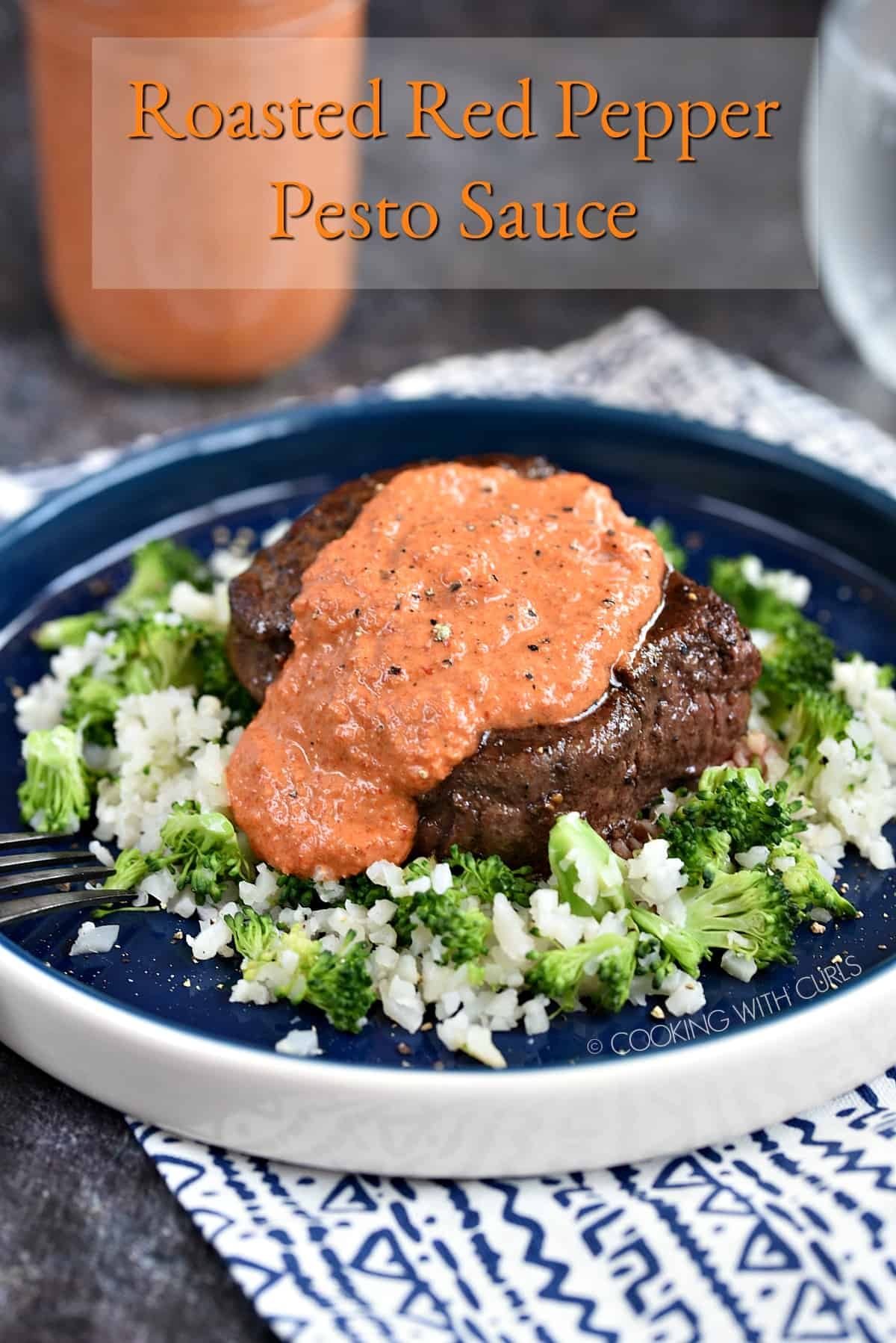 Steak drizzled with roasted red pepper pesto sauce on a bed of cauliflower and broccoli rice sitting on a blue plate.