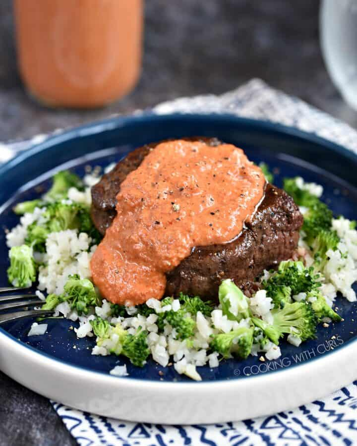 A steak sitting on top of a bed of cauliflower and broccoli rice topped with red pepper peasto sauce.
