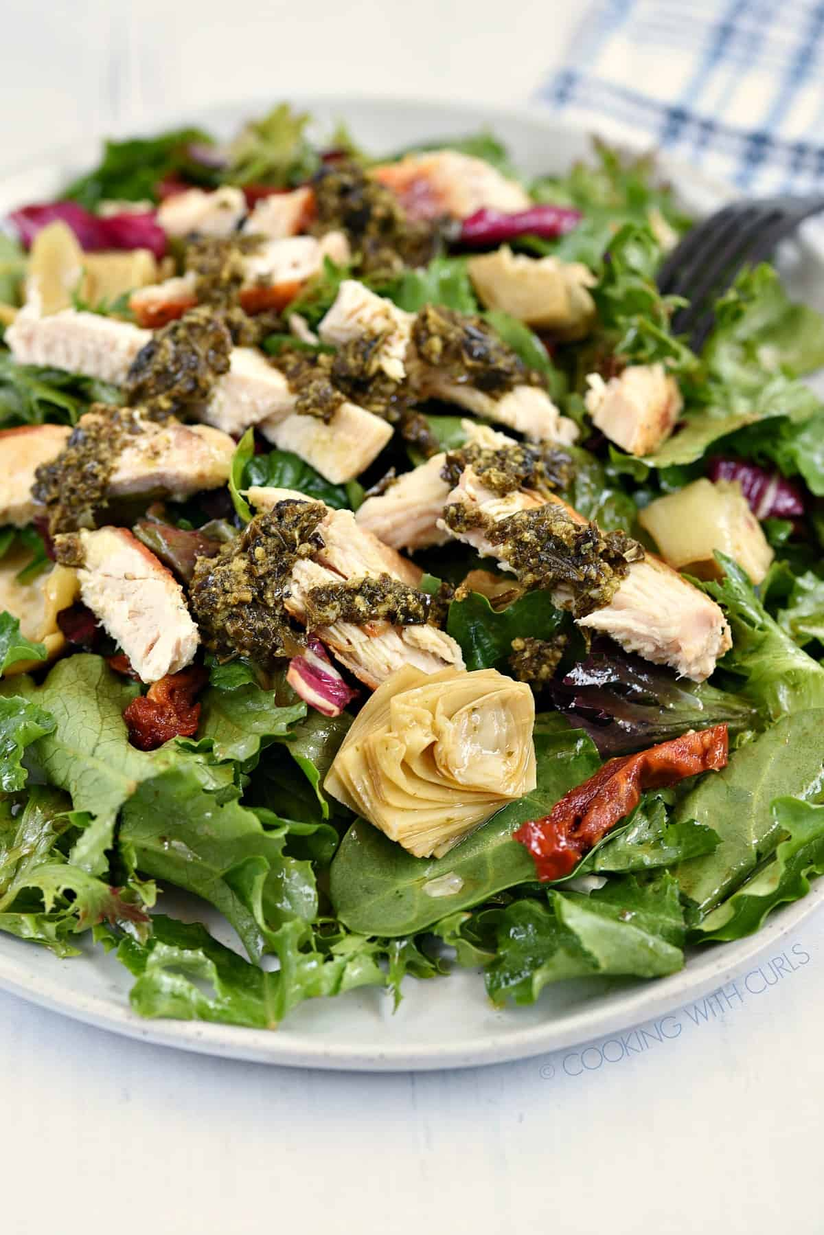 A close-up view of Pesto Chicken Salad on a large white plate.