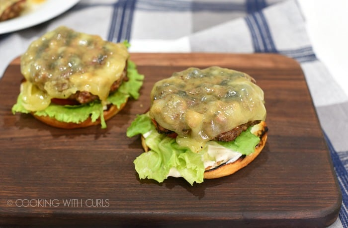 Two buns topped with white barbecue sauce, lettuce, tomato and grilled cheeseburger patties sitting on a walnut cutting board.