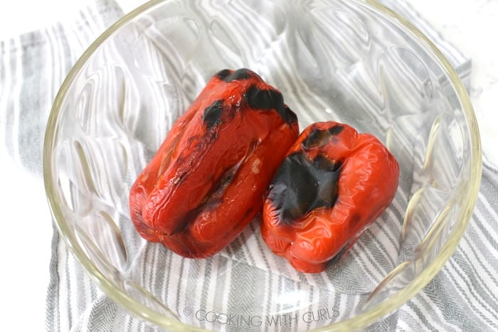 Two charred red bell peppers in a glass bowl.