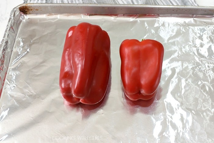 Two red bell peppers on a foil lined baking sheet.